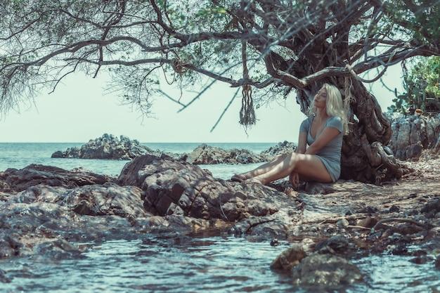 Dromerige blonde jonge vrouw in mini-jurk met koord, zittend op de rotsachtige kust bij het water van de golf