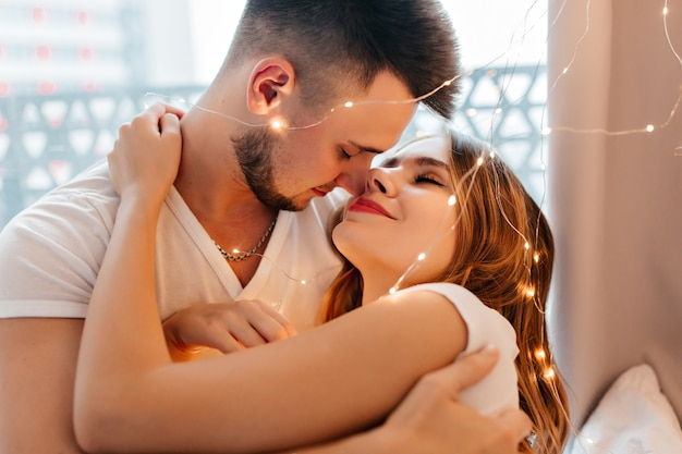 Dromerige blonde vrouw die haar donkerharige echtgenoot zachtjes omhelst. knap mannelijk model kussend blond meisje.