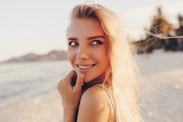 Dromerige blonde vrouw die zich voordeed op het strand