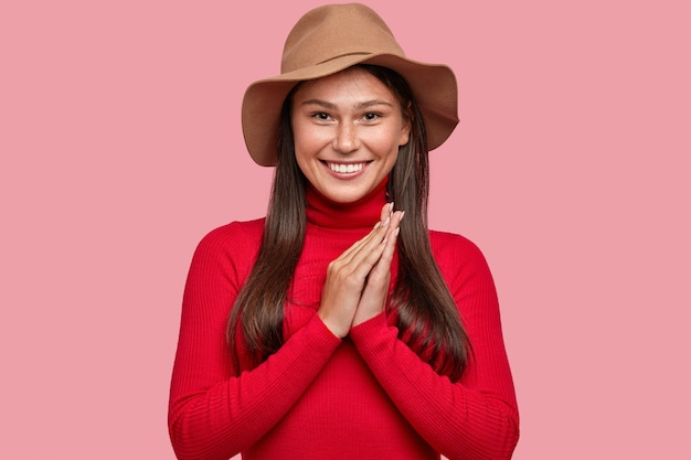 Dromerige brunette jonge vrouw met vrolijke uitdrukking, breed glimlacht, houdt de handen bij elkaar, in een goed humeur