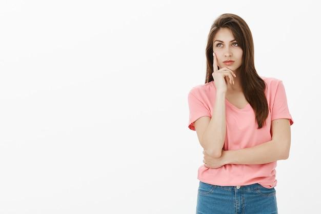 Dromerige brunette vrouw poseren in de studio