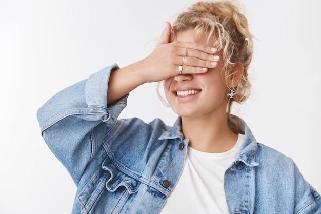 Dromerige creatieve charmante schattige vriendin blond krullend kapsel stijlvolle accessoires spijkerjasje ogen sluiten palm glimlachend breed anticiperend verrassing wachten verjaardagscadeau, verstoppertje spelen