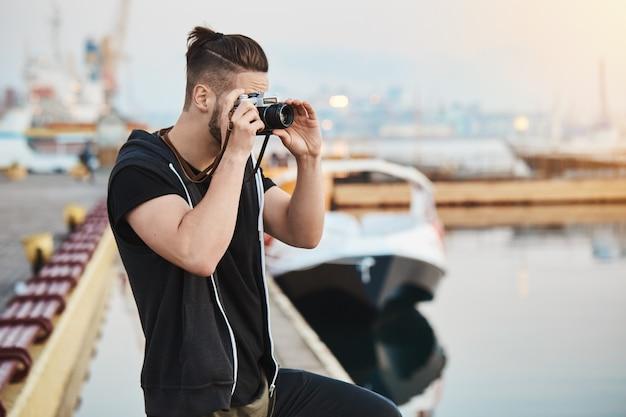 Dromerige creatieve europese fotograaf in stijlvolle outfit staande in de haven, foto van de zee