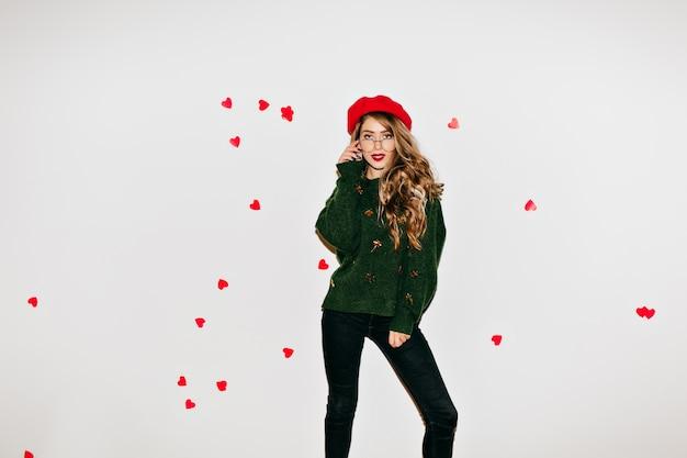 Dromerige dame in baret staande in zelfverzekerde pose tijdens het poseren in valentijnsdag