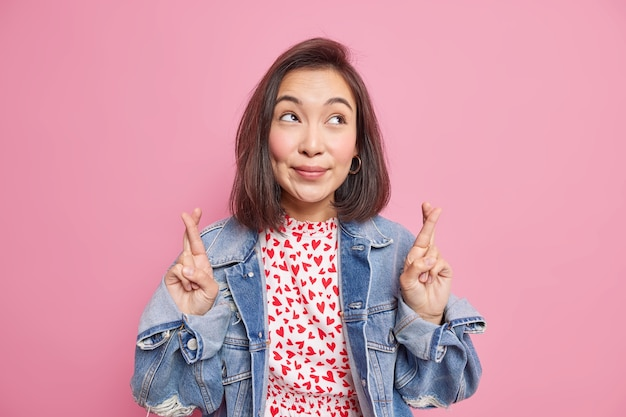 Dromerige donkerharige aziatische vrouw kruist vingers gelooft dat geluk wacht op belangrijke resultaten die hierboven zijn gericht, gekleed in een stijlvol spijkerjack geïsoleerd over roze muur. mogen dromen uitkomen