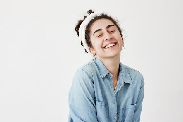 Dromerige donkerharige vrouw heeft een vrolijke uitdrukking, sluit de ogen van vreugde, draagt een spijkerblouse, is blij goed nieuws te ontvangen, glimlacht en toont witte tanden, poseert tegen de witte muur