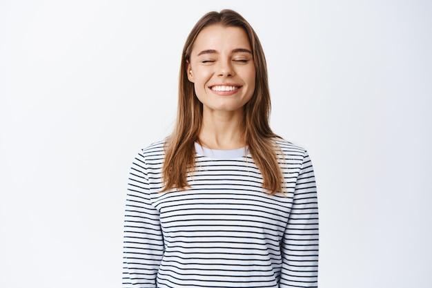 Dromerige en gelukkige mooie vrouw, ogen sluiten en glimlachen, vrij ademen, dagdromen of iets positiefs voorstellen, in casual outfit over witte muur staan