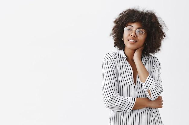 Dromerige en knappe vrouwelijke werkverslaafde met een donkere huidskleur in een gestreepte blouse en een bril die de nek aanraakt zachtjes glimlachend en starend naar de linkerbovenhoek met een tedere en romantische uitdrukking