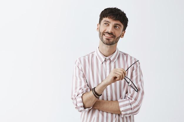 Dromerige en nostalgische stijlvolle bebaarde man die met bril tegen de witte muur poseert