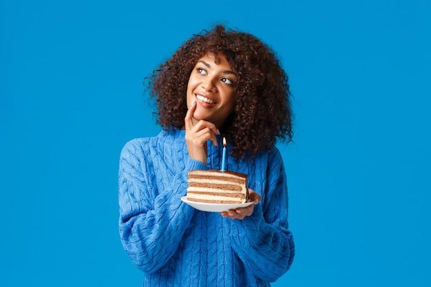 Dromerige en vrolijke, mooie afro-amerikaanse vrouw met een afro-kapsel, nadenkend starend, glimlachend en haar lip aanraken alsof ze nadenkt over de wens voordat ze de kaars in de verjaardagstaart uitblaast.