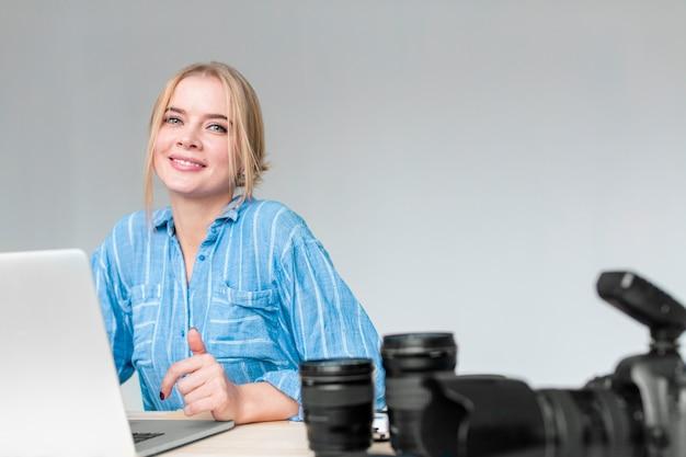 Dromerige fotograafvrouw die aan haar laptop werkt