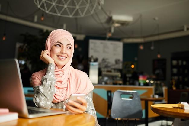 Dromerige gelukkig moslimvrouw met smartphone