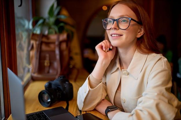 Dromerige gelukkige jonge vrouwelijke fotograaf zit met laptop en camera in café
