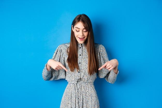 Dromerige, gelukkige vrouw die de vingers naar beneden wijst en zich afvraagt naar de promotie, geweldig nieuws laat zien, staande in jurk op blauw.
