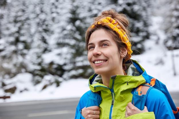 Dromerige gelukkige vrouw met vrolijke uitdrukking, draagt gele hoofddoek en anorak, draagt rugzak