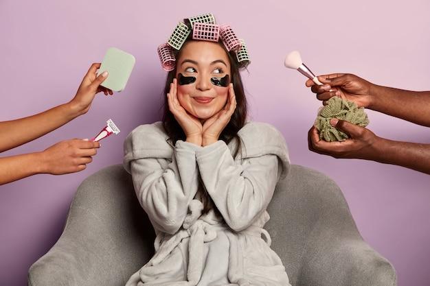 Dromerige gelukkige vrouw poseert met ooglapjes en krulspelden