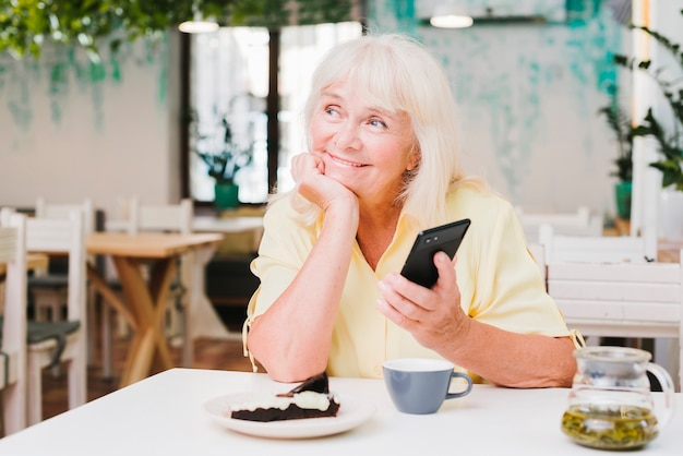 Dromerige glimlachende bejaarde met smartphone
