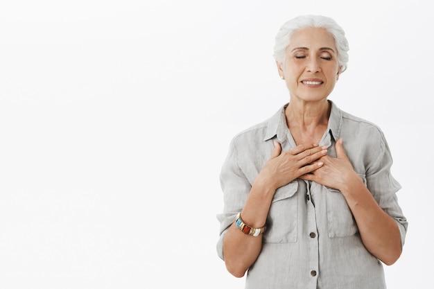 Dromerige glimlachende grootmoeder, oude dame, ogen dicht en handen op hart, dagdromen