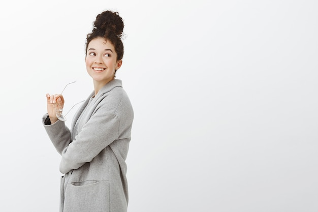 Dromerige, goed uitziende europese stedelijke ondernemer in modieuze grijze jas, staande in profiel en er goed uitziend met een brede, zelfverzekerde glimlach
