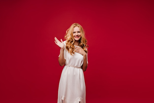 Dromerige goedgehumeurde dame poseren in witte jurk. extatisch langharig meisje geïsoleerd op rode muur.