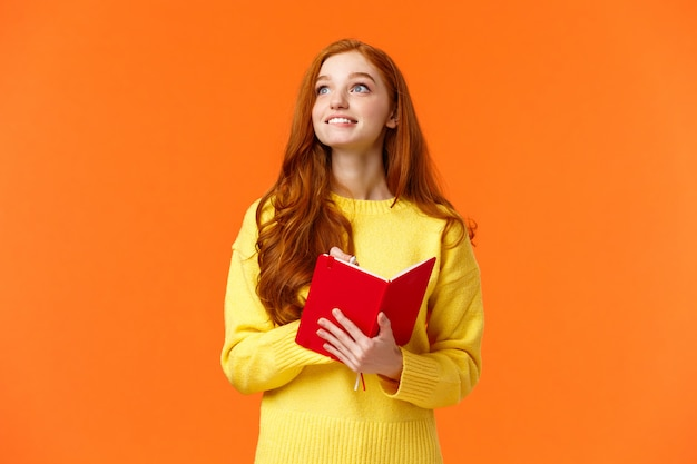 Dromerige, inspirerende schattige roodharige vrouwelijke student die dagelijkse taken schrijft