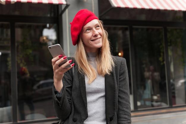 Dromerige jonge aantrekkelijke blonde vrouw in trendy kleding glimlachend sluw terwijl ze naar boven kijkt, smartphone in opgeheven hand houden