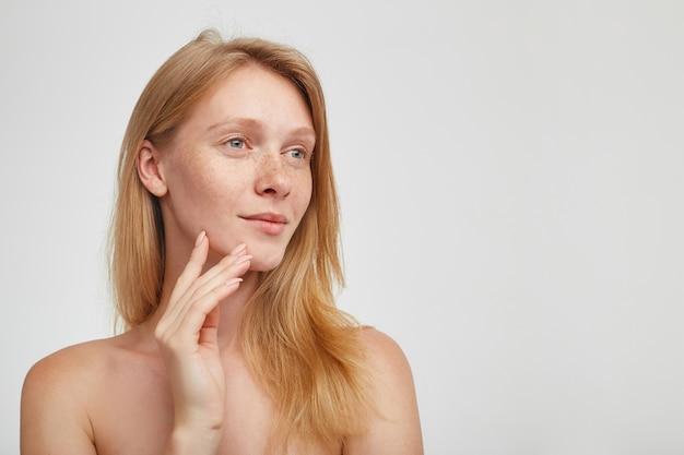 Dromerige jonge aantrekkelijke roodharige vrouw met natuurlijke make-up kijkt positief opzij met een lichte glimlach en houdt opgeheven hand op haar wang, geïsoleerd over witte muur