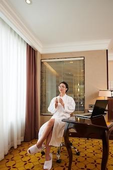 Dromerige jonge aziatische zakenvrouw in badjas zittend met mok aan tafel met laptop en pauze hebben ...