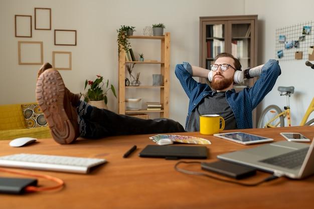 Dromerige jonge bebaarde man zit in een ontspannen positie en luistert naar muziek in de koptelefoon terwijl hij denkt aan een nieuw ontwerpproject