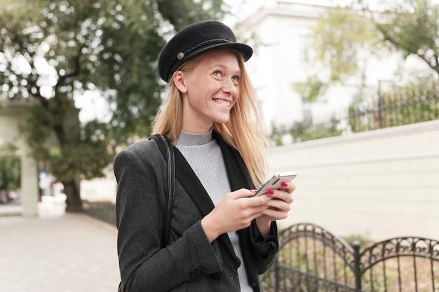 Dromerige jonge positieve blonde vrouw met rode manicure bijt onderlip terwijl ze vrolijk naar boven kijkt en oprecht glimlacht, mobiele telefoon in opgeheven handen houdt terwijl ze buiten poseren