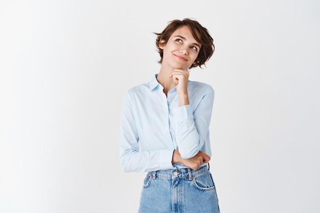Dromerige jonge studente die naar de linkerbovenhoek kijkt, glimlacht en dingen in beeld brengt, staande in een blauw kraagoverhemd op een witte muur