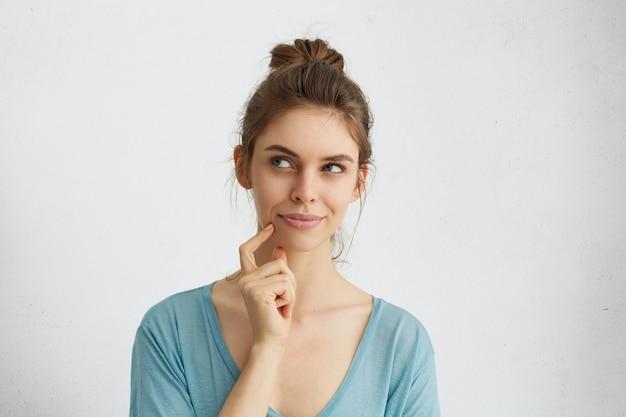 Dromerige jonge vrouw die bedachtzaam opzij kijkt en haar vinger op de kin houdt, ideeën heeft of iets plant