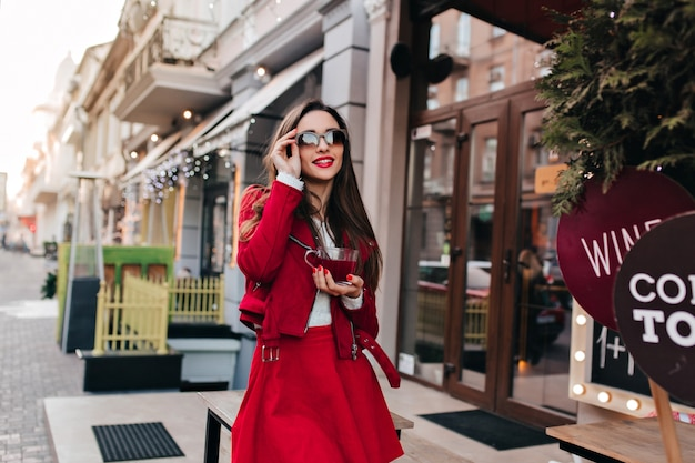 Dromerige jonge vrouw die haar zwarte zonnebril aanraakt terwijl ze over straat loopt