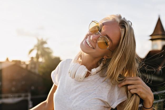 Dromerige jonge vrouw draagt grote witte koptelefoon poseren op hemelachtergrond met schattige glimlach.