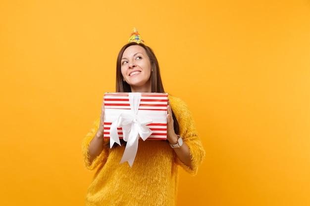 Dromerige jonge vrouw in verjaardagshoed die omhoog kijkt, rode doos met cadeau vasthoudt, aanwezig geniet van vakantie geïsoleerd op felgele achtergrond. mensen oprechte emoties, lifestyle concept. reclame gebied.