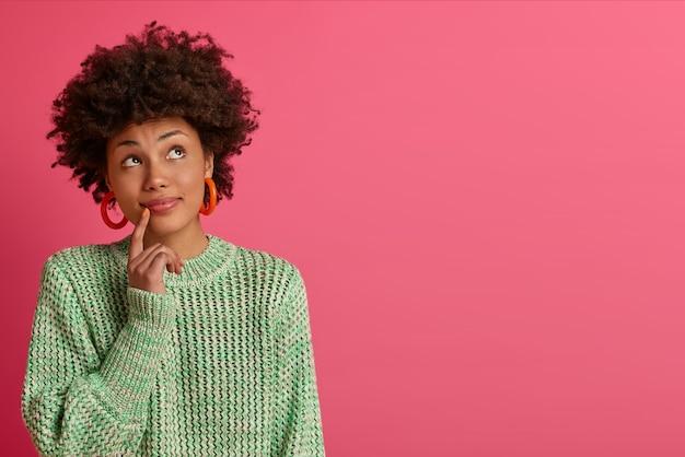 Dromerige jonge vrouw met donkere huid denkt na over carrièremogelijkheden, staat bedachtzaam, geconcentreerd naar boven, gekleed in gebreide trui, geïsoleerd op roze muur, kopieer ruimte voor uw promotie