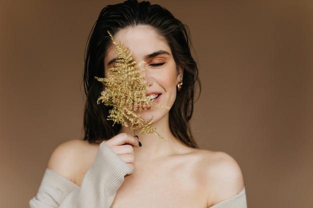 Dromerige jonge vrouw met naakt make-up poseren met plant. close-upportret van extatisch zwartharig meisje koelen.