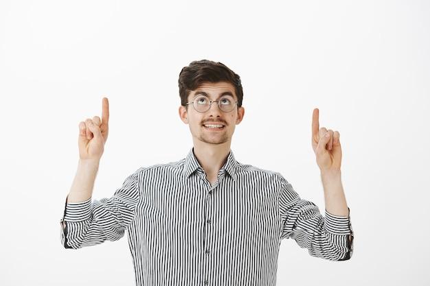 Dromerige knappe gewone man met ronde bril, nieuwsgierig glimlachend terwijl hij kijkt en met wijsvingers naar boven wijst