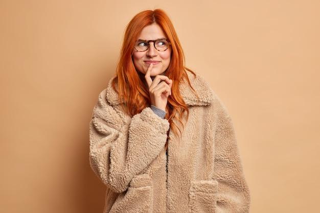 Dromerige knappe vrouw met rood haar kijkt peinzend opzij en draagt een bruine winterjas.