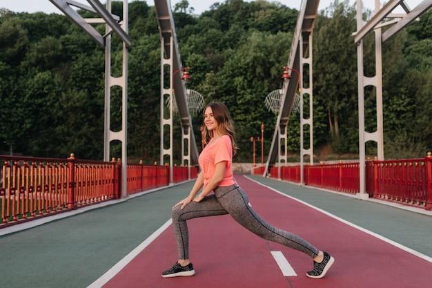 Dromerige krullende vrouw in sportbroek die zich uitstrekt op sintelpad. openluchtportret van romantische meisjestraining
