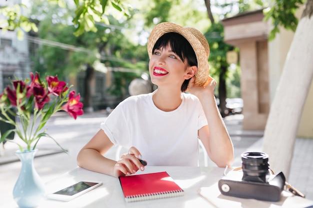 Dromerige lachende meisje met kort kapsel draagt zomer strooien hoed poëzie schrijven tijdens de lunch in de tuin