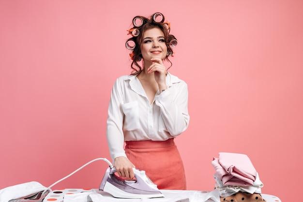 Dromerige, mooie huisvrouw strijkt kleren op de strijkplank