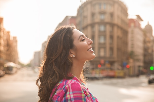 Dromerige mooie vrouw die van het stadsleven geniet