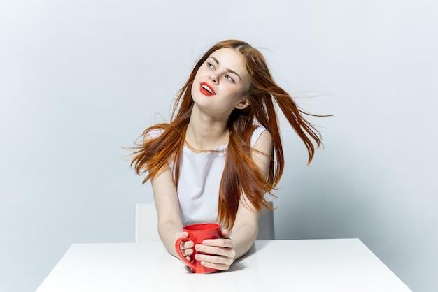 Dromerige mooie vrouw met een koffiekopje