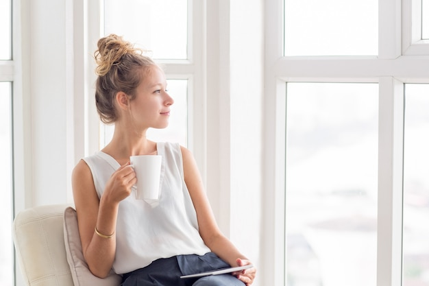 Dromerige mooie vrouw met thee en tablet op loggia