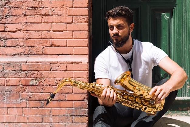Dromerige muzikant poseren met saxofoon