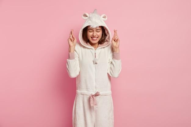 Dromerige positieve jonge vrouw in zacht kigurumi-kostuum, kruist vingers, gelooft in geluk
