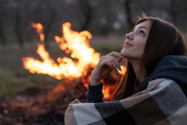 Dromerige romantische brunette meisje in plaid opzoeken, groot kampvuur