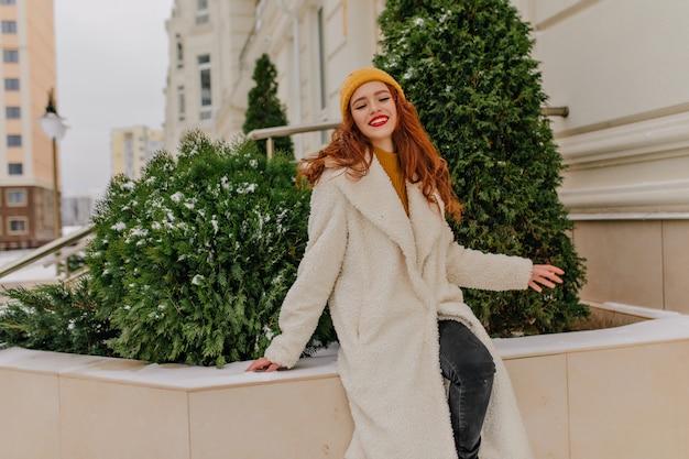 Dromerige roodharige vrouw die zich voordeed op straat in de winterdag. buiten foto van vrolijk kaukasisch meisje positieve emoties uitdrukken.