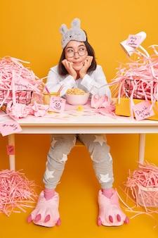 Dromerige schattige aziatische student gekleed in zachte pyjama en slaapmasker op voorhoofd ontbijt op werkplek geniet van gezellige thuisomgeving poses op rommelige desktop met papieren vuilnis gele muur